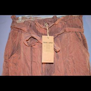 Long burnt orange paper bag pants